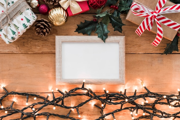 Photo frame between christmas decorations and illuminated fairy lights
