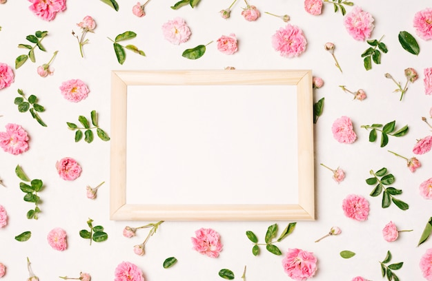 Photo frame between collection of pink flowers and green leaves