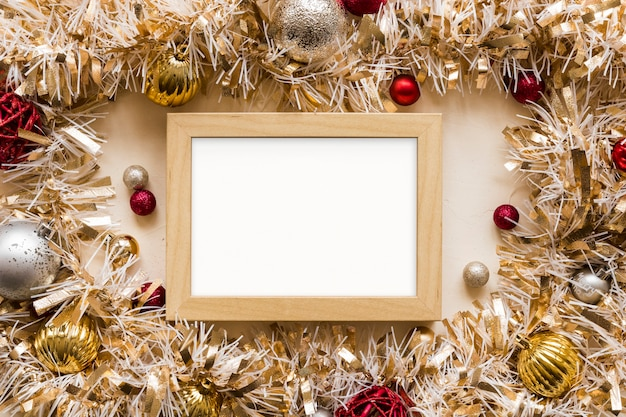 Photo frame between decorative gold tinsel with ornament balls