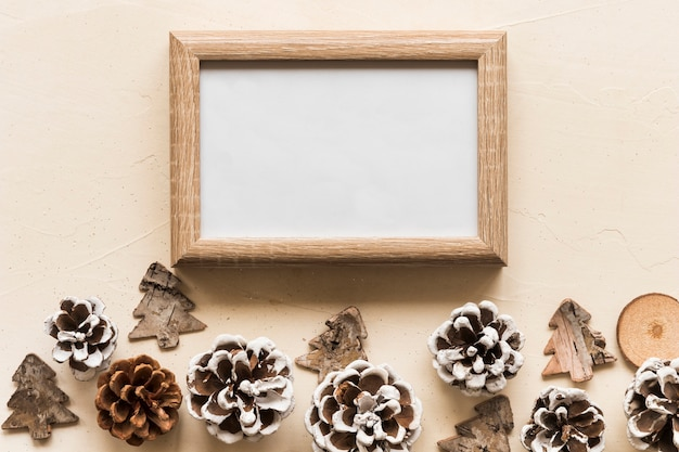 Photo frame between decorative snags and toy fir trees