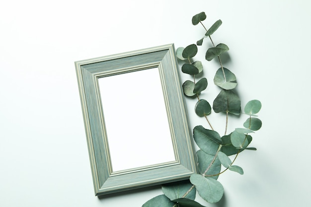Photo frame and eucalyptus branch isolated on white