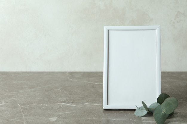 Photo frame and eucalyptus twig on gray textured table against white textured background