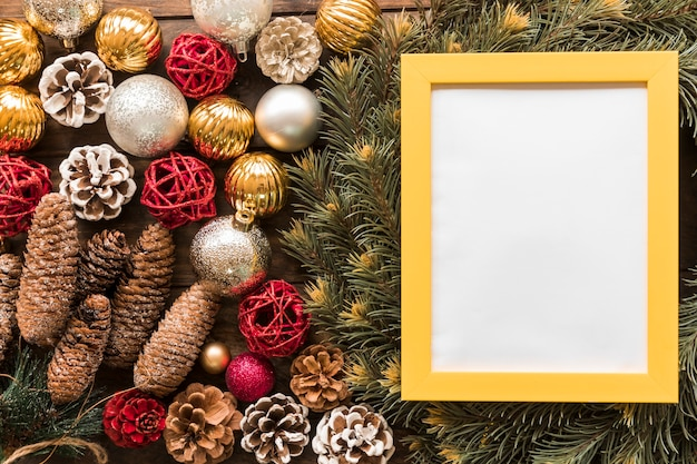Photo frame between fir branches, ornament snags and christmas balls