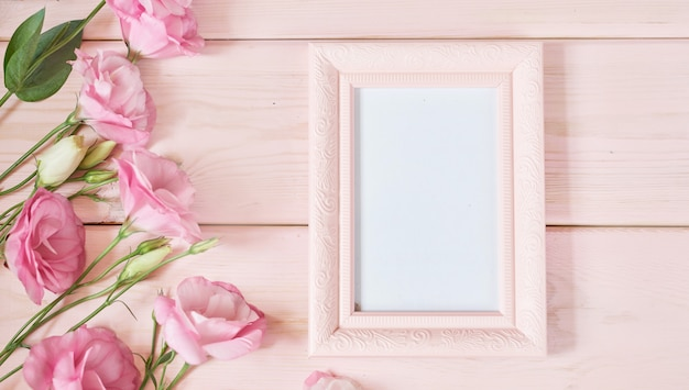 Photo frame and flowers on pink