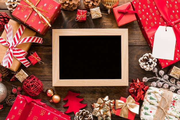 Photo frame between gift boxes and set of christmas decorations