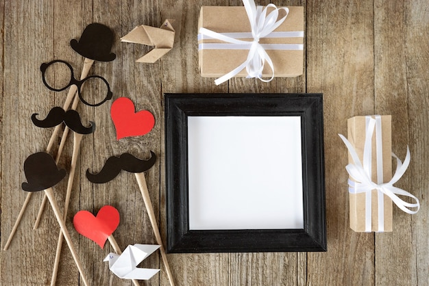 Photo frame and gifts on wooden background for father's holiday.