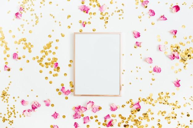 フォト フレームは、白い背景にテキスト、ピンクのバラの花びら、金色の紙吹雪用のスペースをモックアップします。フラットレイ、トップビュー