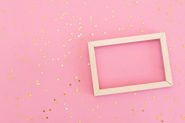 Photo frame mock up with space for text, golden sequins confetti on pink background.