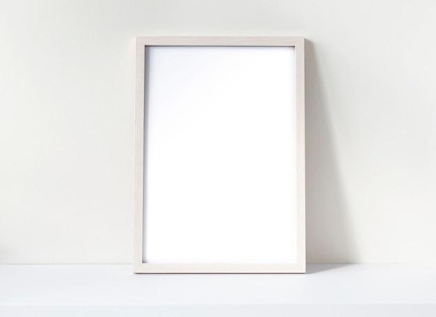흰색 책상에 흰색 빈 시트가 있는 사진 프레임 모형. 소나무 나무 프레임 모형입니다. 텍스트를 위한 공간입니다.