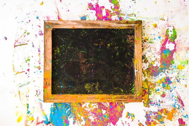 Photo frame near blurs of different bright dry colors