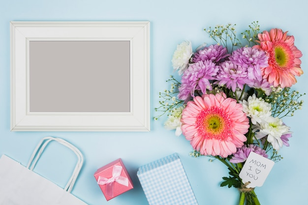 Photo frame near bouquet of fresh flowers with title on tag near packet, present and notebook