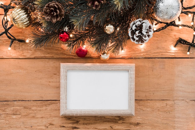 Photo frame near christmas decorations and highlighted fairy lights