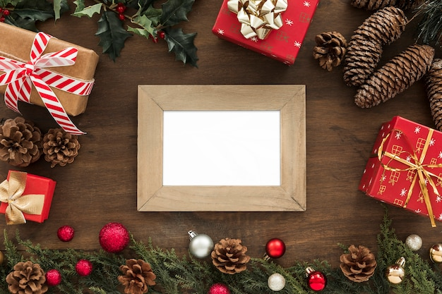Photo frame near fir twigs, snags, presents and christmas toys