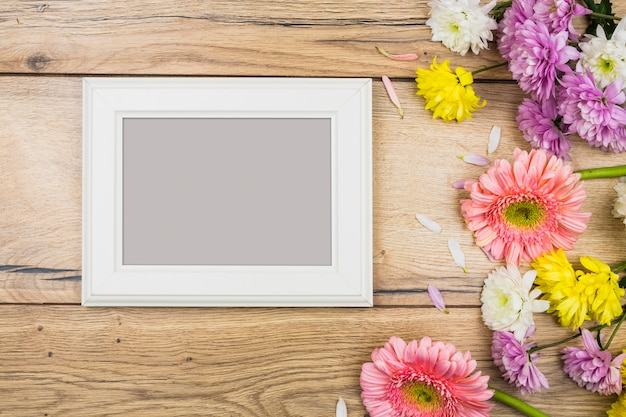 Photo frame near fresh bright flowers on desk