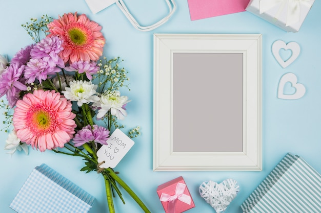 Photo frame near fresh flowers with title on tag and decorations
