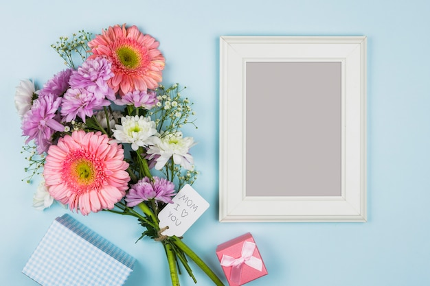 Photo frame near fresh flowers with title on tag near packet, present and notebook