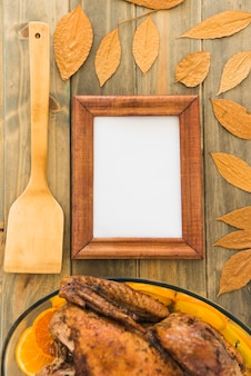 Photo frame near paddle and chicken between dry leaves