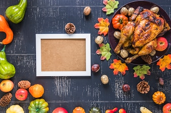 Photo frame near roasted chicken and vegetables