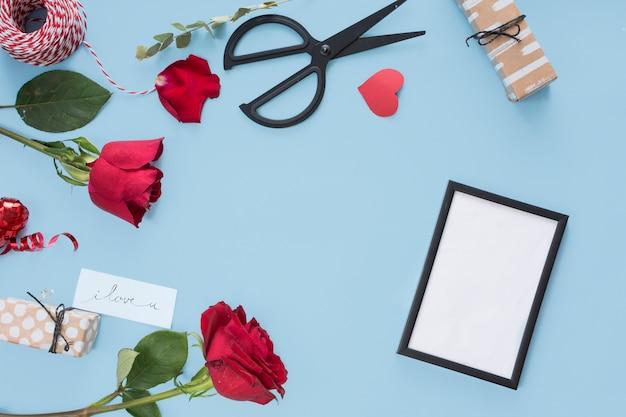 Photo frame near scissors, flowers and bobbin of twists