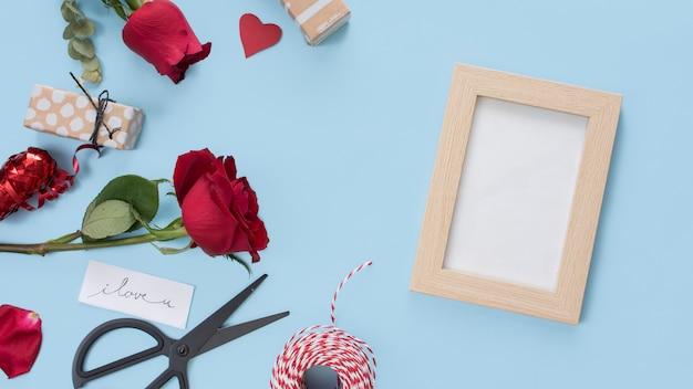 Photo frame near scissors, flowers, tag and bobbin of twists