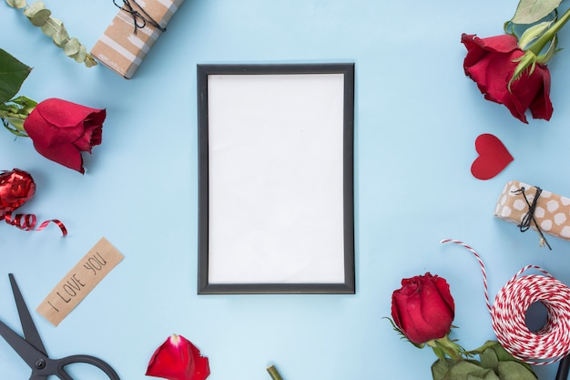 Photo frame near scissors, roses and bobbin of twists