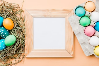 Photo frame near set of bright Easter eggs in nest and container