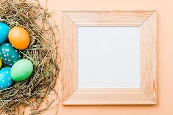 Photo frame near set of bright Easter eggs in nest