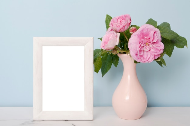 Photo frame near a vase with flowers on a table on blue wall background