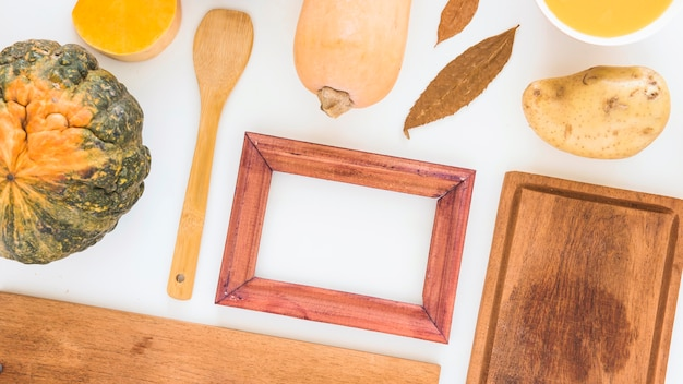 Photo frame near vegetables and cutting board