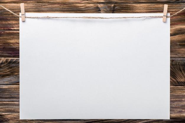 사진 프레임, 메모. 격리 된 흰 텍스처와 비즈니스 사진 프레임입니다. 빈 사진 프레임입니다. 옷 못에 하얀 시트. 나무 배경입니다. 비즈니스, 메모, 판매에 이상적