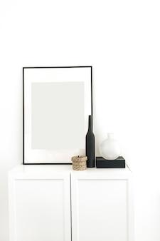 흰 벽에 장식 된 서랍장에 사진 프레임