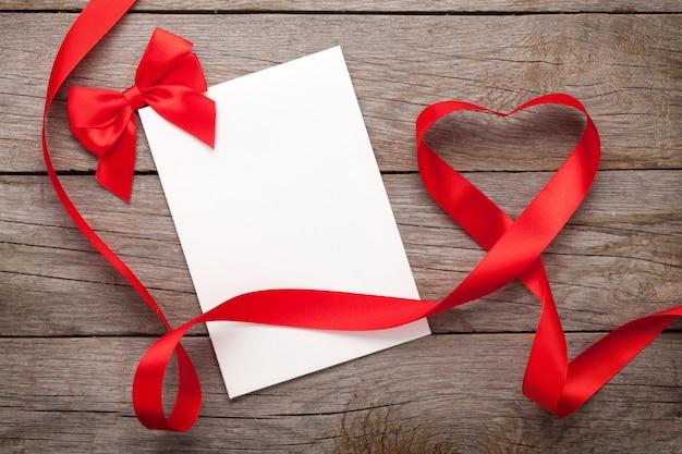 Фоторамка или подарочная карта с лентой в форме сердца на день святого валентина на фоне деревянного стола