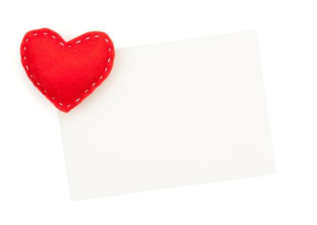 フォトフレームまたはグリーティングカードと手作りのバレンタインデーのおもちゃの心。白い背景で隔離