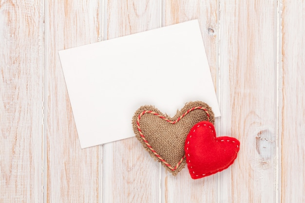 Фоторамка или поздравительная открытка и ручные игрушечные сердечки на день святого валентина на белом деревянном фоне
