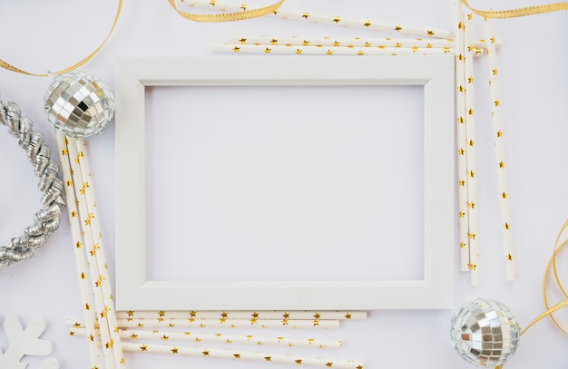Photo frame between ornament wands and balls