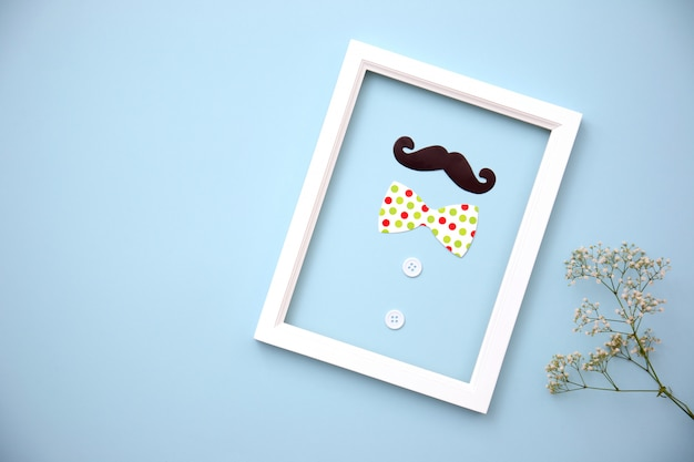 Photo frame, paper mustache, tie on blue pastel background with copy space. happy father's day.
