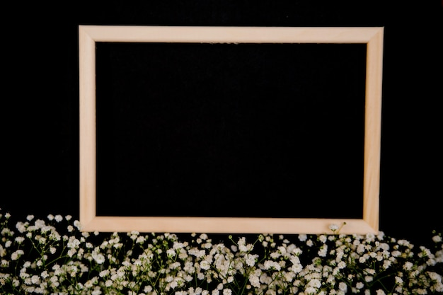 Photo frame and small white flowers on a black background. the white flowers of the gypsophila lie in a row. layout with decorative elements.an empty space for the text.