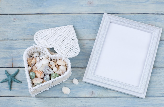 Photo frame, starfish and in a box in the shape of a heart lie seashells