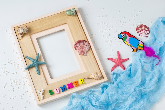 Photo frame, starfish, shells, the word summer, sand and a parrot. about summer vacation, memories
