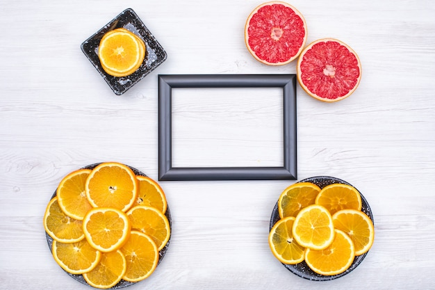 Photo frame surrounded with orange slices in black plate and two slice of grapefruit on wooden  surface