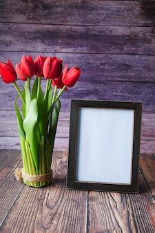 Photo frame and tulip flower on table
