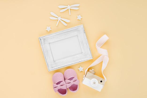 Фоторамка с детскими тапочками и игрушками на желтом фоне. макет текста. набор аксессуаров для новорожденных для девочки. плоская планировка, вид сверху
