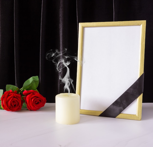 Photo frame with black mourning ribbon, roses and candle