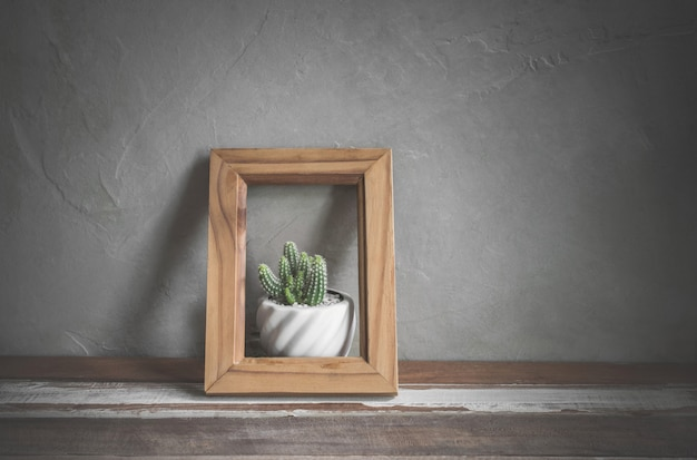 Photo frame with cactus flower on wood table