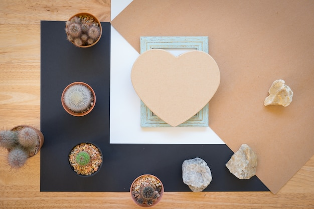 Photo frame  with cactus on wooden background.