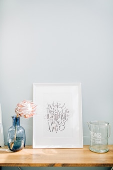 Photo frame with calligraphic quote where there's light there's hope, protea flower in vase in front of pastel blue wall.