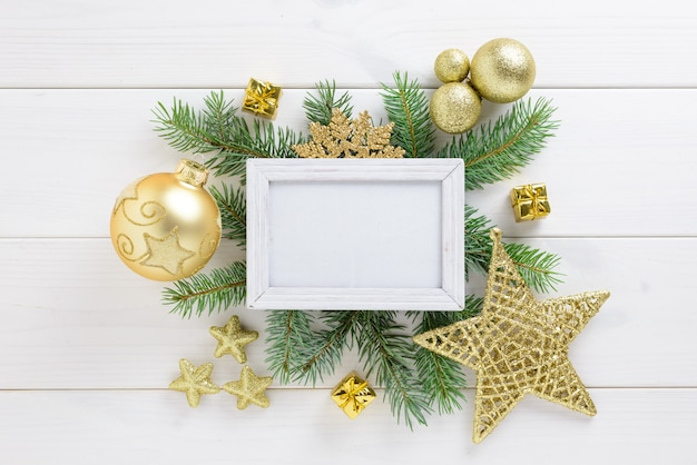 Photo frame with christmas decoration, with golden color balls and star on a white wooden table. top view, frame to copy space