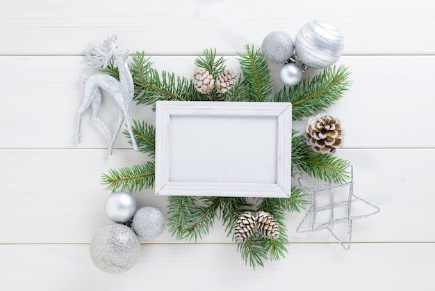 Photo frame with christmas decoration, with white balls and pine cones on a white wooden table. top view, frame to copy space