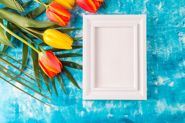 Photo frame with flower bouquet on blue background