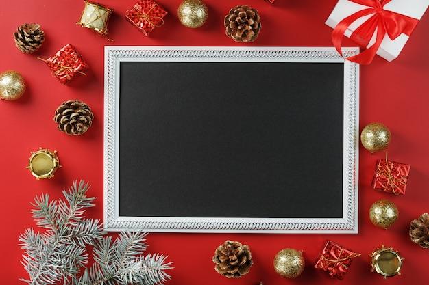 Рамка для фотографий со свободным черным пространством вокруг елочных игрушек и подарков на красном фоне. вид сверху, свободное место для текста